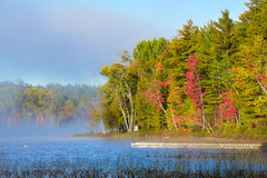 Late summer sun shines on morning misty fog that rises from a lake.  Dock extends into a lake from shore. Late-summer, morning sun shines on mist rising from Royalty Free Stock Photos