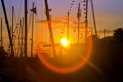 Late sundown at marina with silhouettes and flare effect Royalty Free Stock Photos
