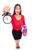 Late on Time. Business Woman in red holding a clock showing 5 to 12 with present, is late on time for shopping Isolated on White Royalty Free Stock Image