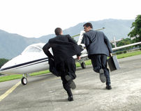 Late to business. Two businessman running towards a plane Royalty Free Stock Photography