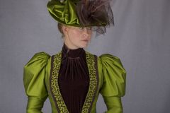 Late Victorian woman in green silk ensemble. A late Victorian 1890`s woman wearing a green silk jacket, hat and skirt with a brown velvet blouse against a white stock images