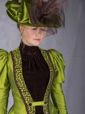 Late Victorian woman in green silk ensemble. A late Victorian 1890`s woman wearing a green silk jacket, hat and skirt with a brown velvet blouse against a white royalty free stock photos