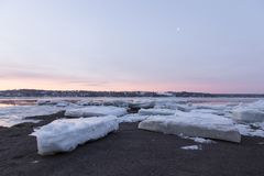 Late winter blue hour sunrise view of large ice chunks on the rocky banks of the St. Lawrence river stock photography