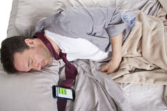 Late For Work. Male sleeping in work clothes and receiving text messages from work Royalty Free Stock Image