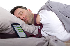 Late For Work. Male sleeping in work clothes and receiving text messages from work Stock Image