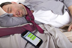 Late For Work. Male sleeping in work clothes and receiving text messages from work Royalty Free Stock Images
