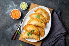 Lateinamerikanische gebratene empanadas mit Tomaten- und Avocadosoßen Beschneidungspfad eingeschlossen lizenzfreies stockbild