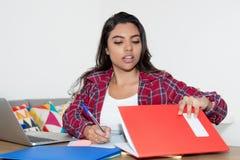Lateinamerikanische Studentin, die am Schreibtisch arbeitet Lizenzfreie Stockfotos