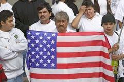 Lateinamerikanischer Mann hält US-Flagge mit Hunderten von den Tausenden Immigranten, die im März für Immigranten und Mexikaner p Lizenzfreie Stockbilder
