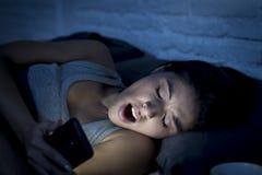 Lateinische Frau auf Bett spät nachts simsend unter Verwendung des Handygähnens schläfrig und müde Stockfotografie