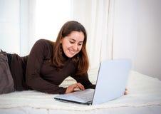 Lateinische Frau des glücklichen braunen Haares, die an ihrem Computer arbeitet Lizenzfreie Stockfotos