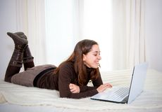 Lateinische Frau des glücklichen braunen Haares, die an ihrem Computer arbeitet Stockbild