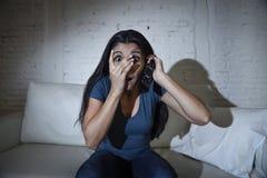 Lateinische Frau, die zu Hause Sofacouch in aufpassendem furchtsamem Horrorfilm des Wohnzimmers Fernsehsitzt Lizenzfreie Stockfotos