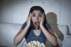 Lateinische Frau, die zu Hause Sofacouch in aufpassendem furchtsamem Horrorfilm des Wohnzimmers Fernsehsitzt Lizenzfreie Stockbilder