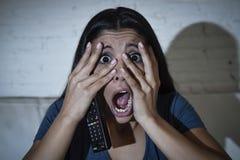 Lateinische Frau, die zu Hause Sofacouch in aufpassendem furchtsamem Horrorfilm des Wohnzimmers Fernsehsitzt Lizenzfreies Stockfoto