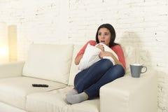 Lateinische Frau, die zu Hause Sofacouch in aufpassendem furchtsamem Horrorfilm des Wohnzimmers Fernsehsitzt Lizenzfreie Stockfotografie