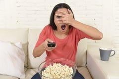 Lateinische Frau, die zu Hause Sofacouch in aufpassendem furchtsamem Horrorfilm des Wohnzimmers Fernsehsitzt Stockfoto