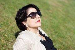 Lateinische Frau mit der Sonnenbrille, die ihr Gesicht in Richtung zur Sonne dreht lizenzfreie stockfotografie