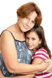 Lateinische Großmutter, die ihre Enkelin umarmt Stockbild