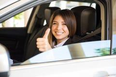 Lateinische junge Frau liebt ihren Neuwagen Stockbild