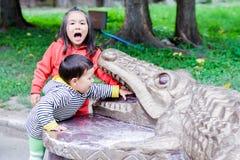 Lateinische kleine Geschwister, die die Zähne des Monuments eines Krokodils schreien und berühren Lizenzfreie Stockfotografie