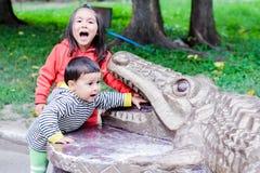 Lateinische kleine Geschwister, die die Zähne des Monuments eines Krokodils schreien und berühren Stockbild