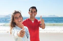 Lateinische Paare am Strand, der sich Daumen zeigt Stockfotografie