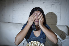 Lateinische Sofacouch der Frau zu Hause Bedeckungsaugen des Wohnzimmers in den aufpassenden Fernseherschrocken Stockbilder