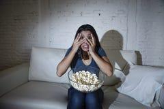 Lateinische Sofacouch der Frau zu Hause Bedeckungsaugen des Wohnzimmers in den aufpassenden Fernseherschrocken Stockfotografie