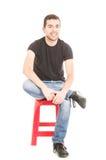 Lateinischer junger Mann, der auf rotem Schemel sitzt Lizenzfreie Stockbilder