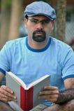 Lateinischer Mann, der ein Buch liest Stockbild