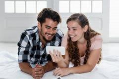 Lateinischer Mann, der am Telefon mit kaukasischer Freundin fernsieht Stockfotos