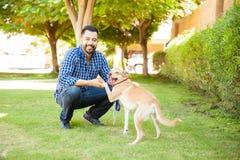 Lateinischer Mann, der versucht, seinen Hund auszubilden Lizenzfreie Stockfotos