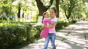 Lateinisches Gehen des Brunette Kind des kleinen Mädchens in den Park mit ihrer Spielzeugpuppe stock video