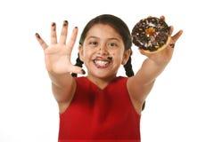 Lateinisches junges Mädchen im roten Kleid, das Schokoladendonut mit den Händen und Mund befleckt und das schmutzige darstellende stockbilder
