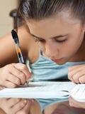 Lateinisches Mädchen, das an ihrer Schuleheimarbeit arbeitet Lizenzfreies Stockfoto