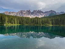 Latemar mount and woods reflected in Karersee lake, Dolomites, Italy Stock Images