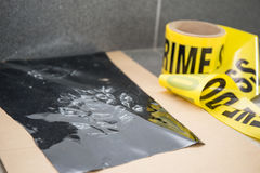 Latent footprint evidence with crime scene tape in crime scene i. Nvestigation stock photo