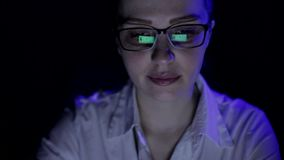 Later a woman working at a laptop, monitor reflection in the glasses. Later a woman working at a laptop, monitor reflection in the glasses stock footage