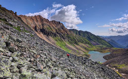 Lateral moraine and the woman hiker climbing foot along the moraine Stock Photography