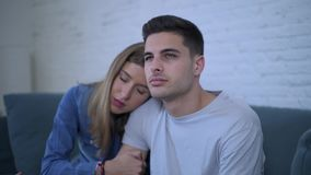 Lateral pan shot of young attractive couple with boyfriend sad frustrated and depressed at home couch and girlfriend comforting. And consoling him in stock video footage