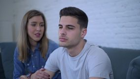 Lateral pan shot of young attractive couple with boyfriend sad frustrated and depressed at home couch girlfriend comforting him stock video footage