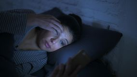 Lateral panning shot of young attractive hispanic woman on her 30s lying in bed late night using mobile phone look stock video footage