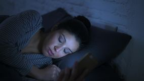 Lateral panning shot of young attractive hispanic woman on her 30s lying in bed late night using mobile phone look. Low light video lateral panning shot of young stock footage