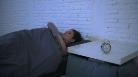 Lateral panning shot of young attractive hispanic woman upset in stress and insomnia lying anxious on bed and trying to sleep. Lateral panning shot of young stock footage