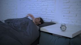 Lateral panning shot of young attractive hispanic woman upset in stress and insomnia lying anxious on bed and trying to sleep stock video