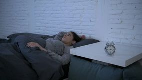 Lateral panning shot of young attractive hispanic woman upset in stress and insomnia lying anxious on bed and trying to sleep stock footage