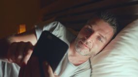 Lateral panning shot of Young attractive and relaxed man at home bedroom networking late night on bed using mobile phone stock video