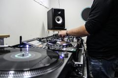 Young guy playing and mixing music on a DJ controller stock photo