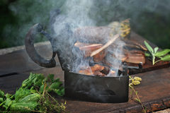 Lateral view on a vintage iron used to barbecue smoked bacon Royalty Free Stock Photos